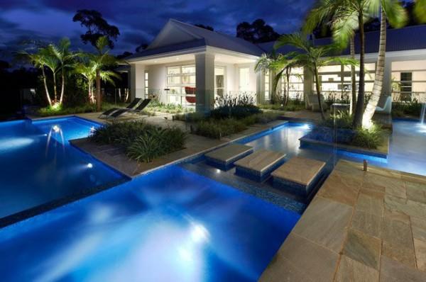 Hãng thiết kế Rolling Stone Landscapes thì mang đến cho ngôi nhà hiện đại ở NSW, Australia một bầu không khí sang trọng và thư thái theo phong cách các khu resort. Bể bơi rộng bao quanh nhà được chia nhỏ bằng các bậc đá xen lẫn với cây, lại có cả có hệ thồng đèn ngầm đẹp như mơ thế này quả khiến người ta phải hâm mộ.