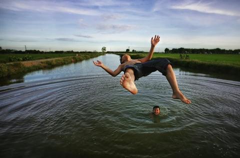 Chung khảo hạng mục Con người: Ảnh của Trần Việt Phương chụp một cậu bé nhảy xuống nước khi đi bơi cùng bạn ở Nghiêm Xuyên, Thường Tín, Hà Nội vào tháng 8/2014, bằng máy Canon EOS-1Ds Mark III.