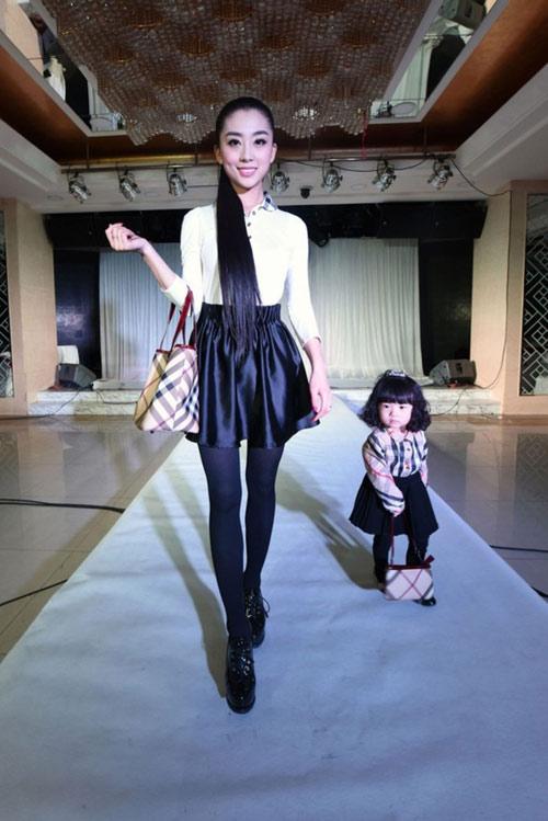 Hình ảnh cô bé và mẹ trong buổi trình diễn thời trang trên sân khấu được đặt tại một khách sạn