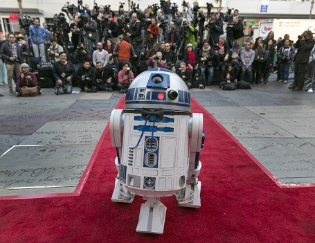 """Rất đông phóng viên đã có mặt để theo dõi hôn lễ của cặp đôi """"fan cuồng Star Wars"""", nhà sản xuất phim đã cử nhân vật robot R2-D2 tới dự hôn lễ. Robot R2-D2 đã đeo nơ và bước đi trên thảm đỏ rất ấn tượng."""