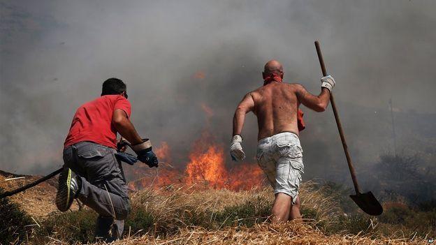 Các công nhân cố gắng dập tắt ngọn lửa. (Ảnh: AP)