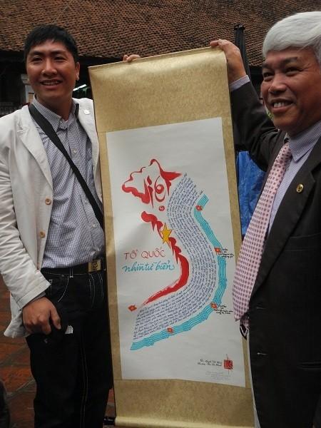"""Các nhà thơ đứng bên tác phẩm """"Tổ quốc là tiếng mẹ"""" của tác giả Nguyễn Văn Chiến."""