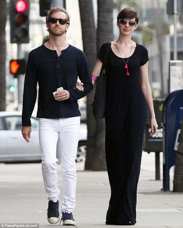 Anne tự tin sánh bước bên chồng trong váy đen dài, với vòng cổ đỏ làm điểm nhấn.