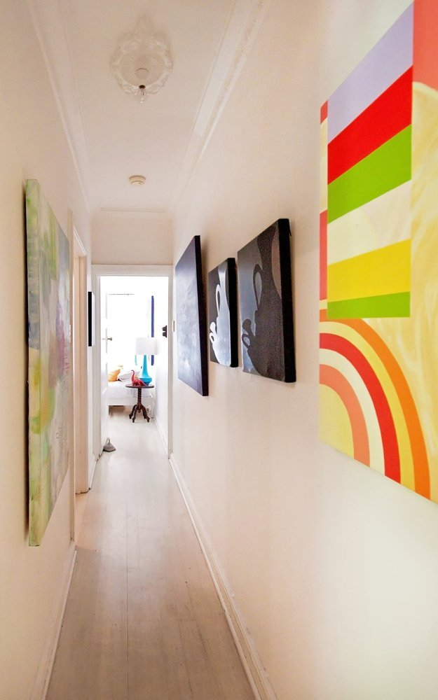 Dọc hành lang được treo nhiều bức tranh với các màu sắc khác nhau.