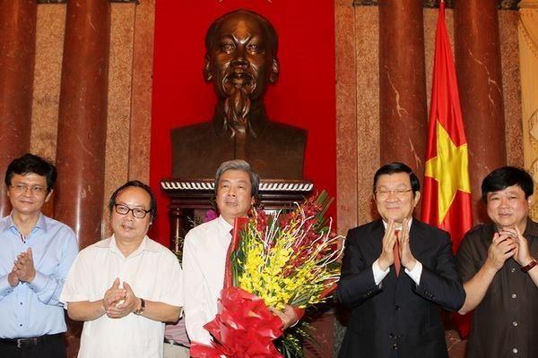Chủ tịch nước Trương Tấn Sang tặng hoa chúc mừng những người làm báo Việt Nam. (Ảnh:TTXVN)