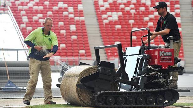 Các nhân viên trải cỏ lên mặt sân vận động quốc gia Singapore.
