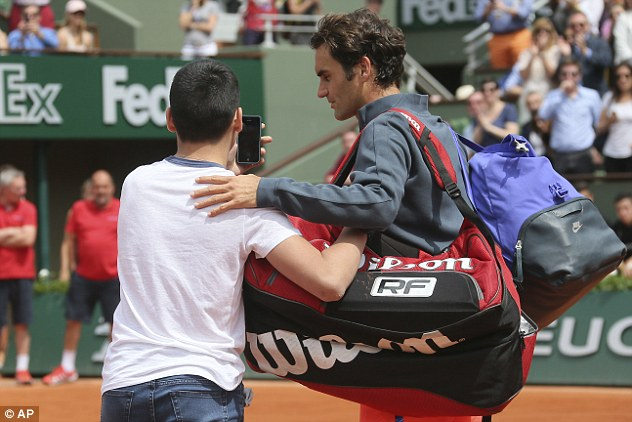 Federer cảm thấy bất tiện khi một cậu bé áp sát và xin chụp ảnh chung ngay trên sân.