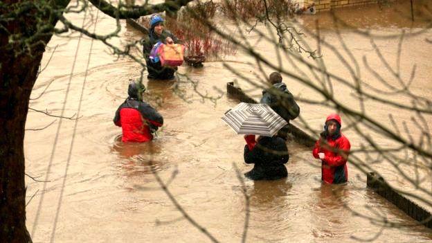 Người dân mang theo chút tài sản vượt qua những con phố bị ngập lụt ở Mytholmroyd, West Yorkshire.