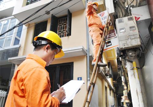 Nhân viên Công ty Điện lực Hoàn Kiếm đang ghi chỉ số công tơ cho khách hàng. (Ảnh: Zing)