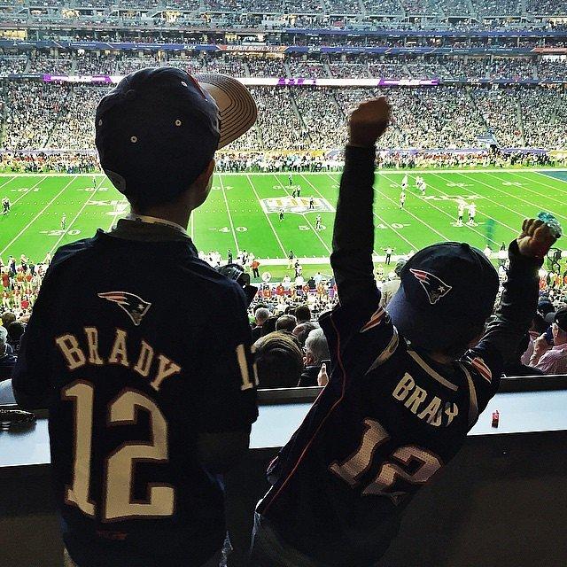 Người mẫu Brazil Gisele Bundchen chụp ảnh hai cậu con trai chăm chú theo dõi trận so tài đỉnh cao giữa hai đội Patriots và Seahawks tại Super Bowl 2015