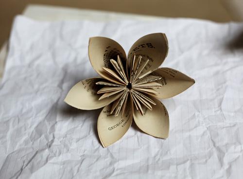 Giấy sách, báo được gấp thành bông hoa xinh xắn để bày trang trí hay đính, tô điểm thêm cho một số đồ khác.