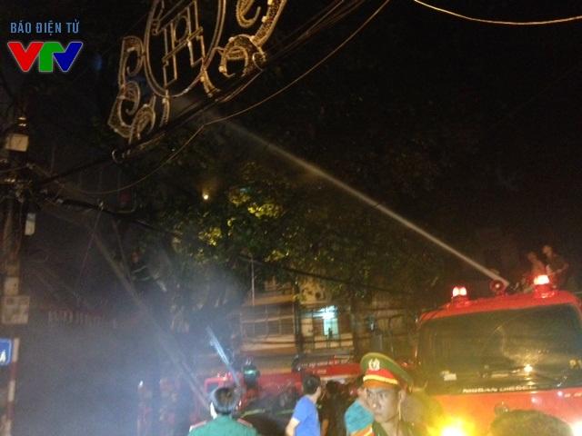Vòi phun nước từ xe cứu hỏa cố gắng dập lửa trên tầng 2 ngôi nhà