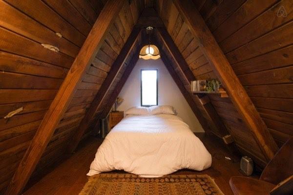 Phòng ngủ đơn giản với cửa sổ lớn, giường ngủ đặt giữa phòng và một chiếc giá kê đồ trên tường.