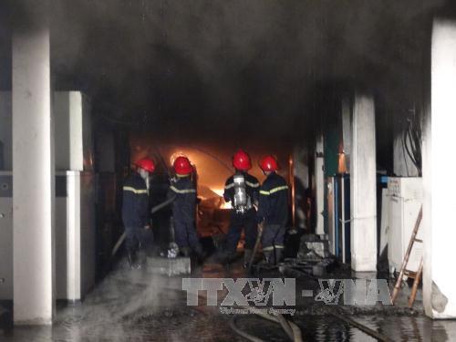 Lực lượng Cảnh sát PCCC nỗ lực dập ngọn lửa đang bùng cháy mạnh tại Công ty JITECH Vina. (Ảnh: Thái Hùng/TTXVN)