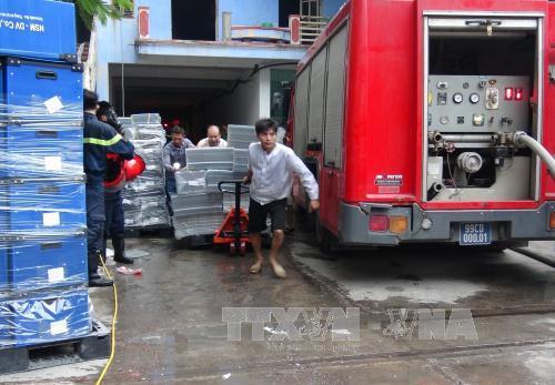Khẩn trương di rời hàng hóa ra khỏi hiện trường vụ cháy. (Ảnh: Thái Hùng/TTXVN)