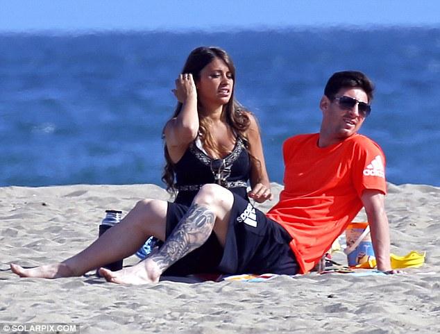 Messi và bạn gái Roccuzzo dõi theo cậu cả Thiago đang chơi trên bãi biển.