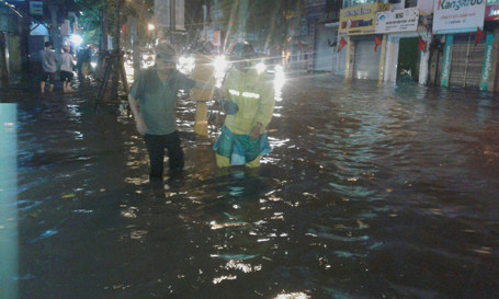 Công nhân Công ty Thoát nước giúp người già qua đường bị ngập nặng.