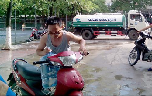 Nhiều người dân đến chợ Láng Hạ A để xin nước sạch.Ảnh: Sơn Dương/VnE