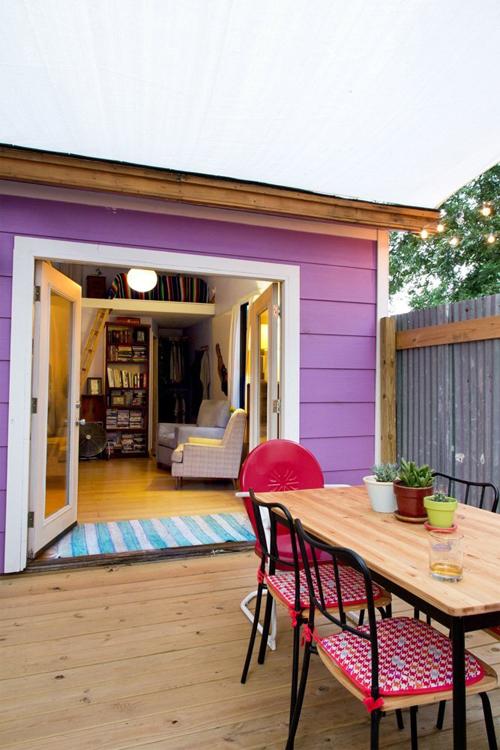 Ngôi nhà được sơn tường ngoài màu tím nổi bật, với khoảng sân nhỏ trước nhà để nghỉ ngơi.