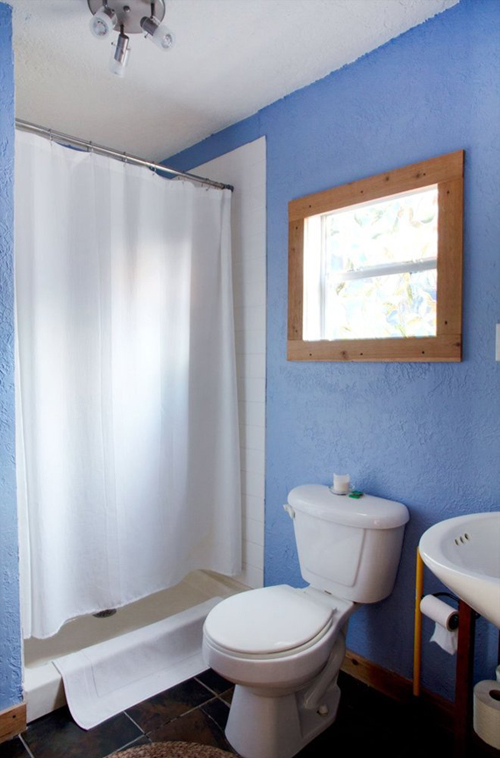 Phòng tắm có tường được sơn màu xanh tím, tạo cảm giác dễ chịu.