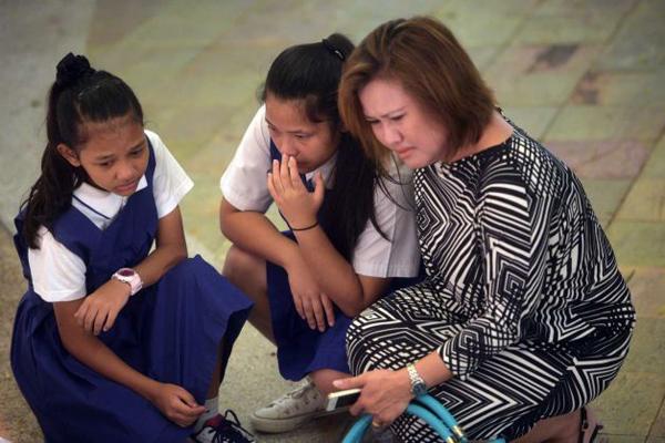 Một người phụ nữ cùng hai con gái khóc nghẹn trước sự ra đi của cựu Thủ tướng.