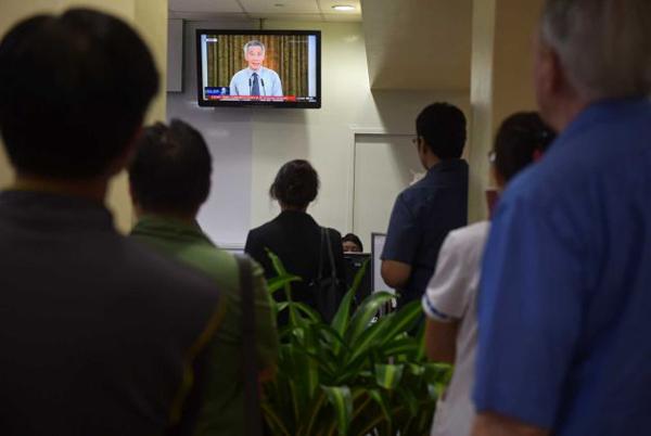 Những người có mặt trong bệnh viên bần thần trước chương trình phát sóng trực tiếp về sự ra đi của ông Lý Quang Diệu trên truyền hình.