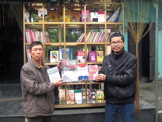Anh Nguyễn Quang Thạch bên tủ sách nông thôn (Ảnh do nhân vật cung cấp).