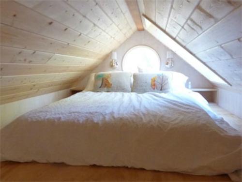 Giường ngủ được đặt trên tầng áp mái, có cửa sổ hình tròn.