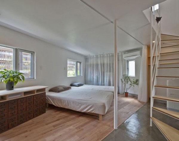 Giường ngủ nằm gần cầu thang dẫn lên tầng trên.