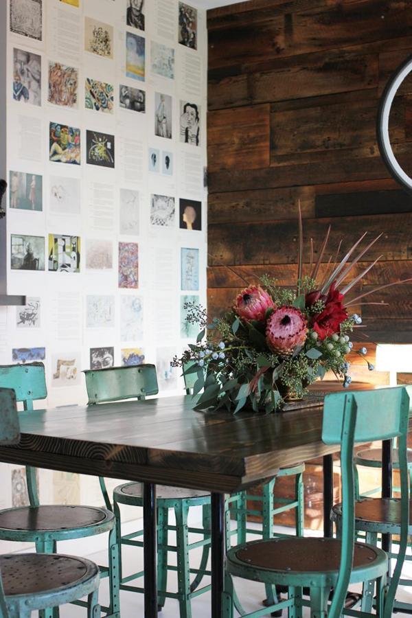 Bức tường bên bàn ăn được tô điểm sinh động bởi nhiều tranh, ảnh của sách, báo.