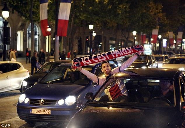 CĐV PSG ăn mừng khi đang lưu thông trên đường phố Paris.