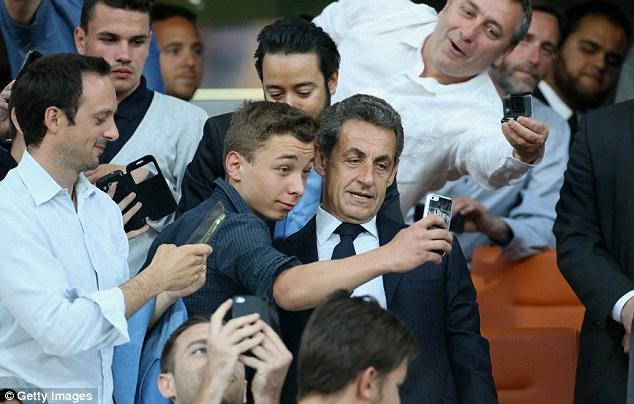 CĐV nhí chụp ảnh selfie với cựu Tổng thống Nicolas Sarkozy có mặt trên khán đài.