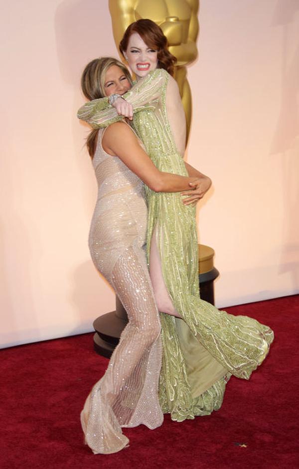 Jennifer Aniston cố gắng nhấc bổng đàn em Emma Stone trên thảm đỏ Oscar.