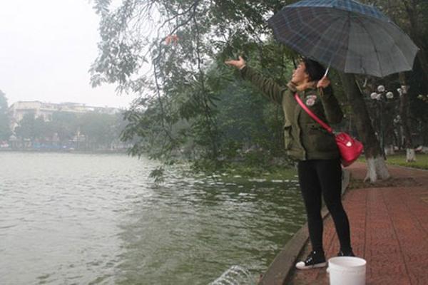 Vì mưa rét nên nhiều người phải che ô đứng thả cá (ảnh: Báo Công Lý)