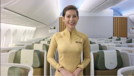 Tiếp viên phục vụ khoang khách hạng thương gia mặc áo dài màu vàng nhẹ.