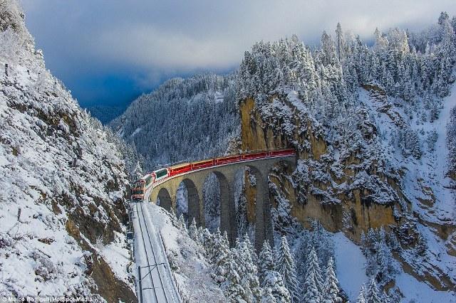 Nằm ở độ cao 65 mét trong dãy Alps, những toa xe màu đỏ nổi bật trên nền trắng tinh khiết của tuyết