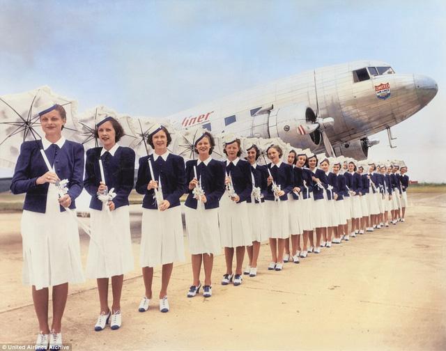 Các nữ tiếp viên của hãng hàng không United Airlines đội mũ, váy và áo jacket, xếp hàng dài chụp trước máy bay. Hình ảnh chụp năm 1939.