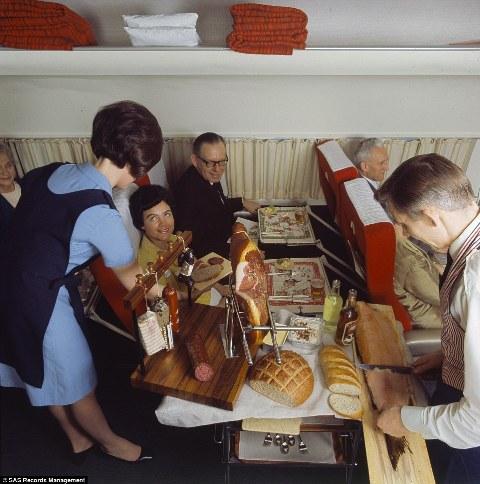 Một góc nhìn khác vào xe phục vụ đồ ăn năm 1969, một thành viên của phi hành đoàn đang lọc phần phi lê cá hồi trong khi người khác đang phục vụ khách với xúc xích và bánh mì nướng giòn