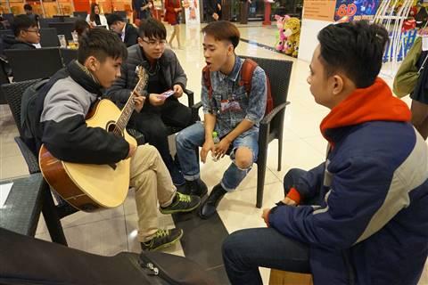 Một nhóm ngồi bên ngoài đàn hát thu hút rất nhiều người tới xem