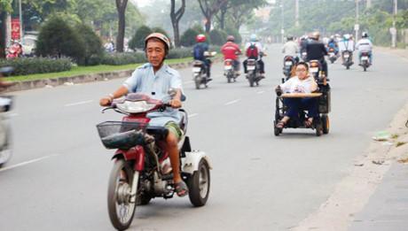 Ông Hoàng Việt Tiến đi xe ba bánh dẫn đường cho con trai Hoàng Việt Tuấn đi xe lăn đến trường.