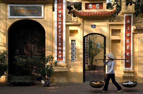Một người phụ nữ gồng gánh đi ngang qua chùa Lý Quốc Sư, Hà Nội.
