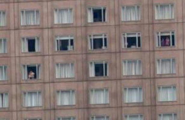 """Với dáng đứng 1 chân gác lên bậc cửa sổ, người đàn ông này có vẻ rất thư giãn với tư thế """"không một mảnh vải che thân""""."""