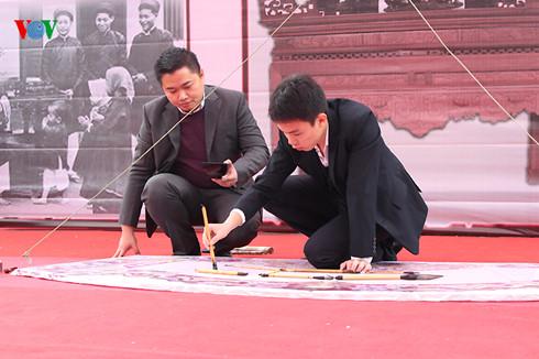 Trạng nguyên thư pháp Nguyễn Tô Tâm An (sinh năm 1997) biểu diễn 4 chữ Yến Dực Di Mưu trên hoành phi
