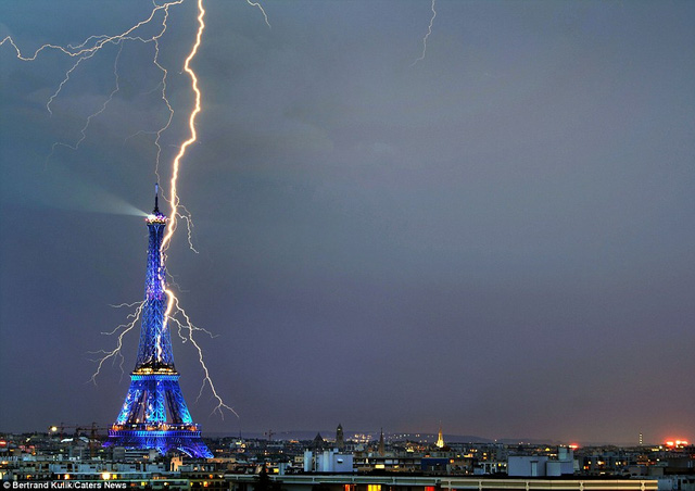 Tháp Eiffel được thắp sáng lên màu xanh huyền diệu khi một tia chớp hình zic zac đánh qua.