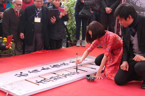 Nữ thư pháp gia Nguyễn Hoài Thu (sinh năm 1985), cựu sinh viên khoa Trung - Đại học Hà Nội, biểu diễn đôi câu đối.