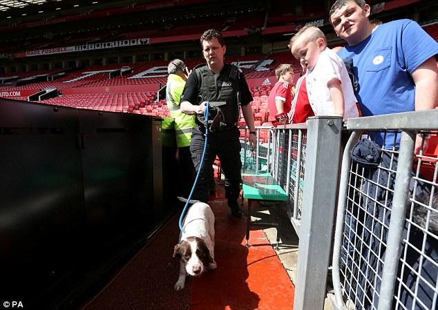 Nhân viên an ninh đưa chó nghiệp vụ đến sân Old Trafford sau khi một bọc lạ nghi là bom được phát hiện ở hướng Tây Bắc trên khán đài.