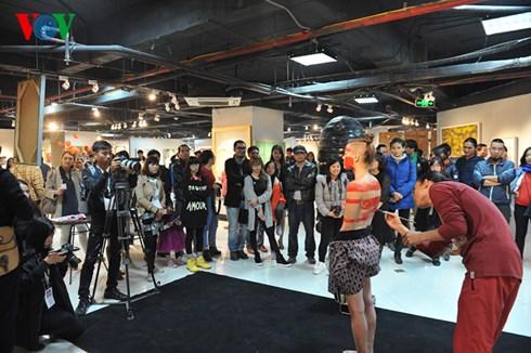Khán giả chăm chú xem màn biểu diễn body art tại lễ khai mạc.
