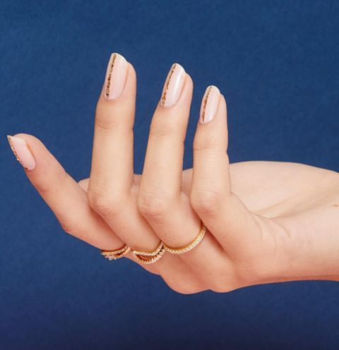 Một bộ móng tay với tông màu hồng nude chủ đạo và những sọc kẻ vàng đơn giản sẽ kết hợp hài hòa với trang sức màu đồng hay màu vàng hồng.