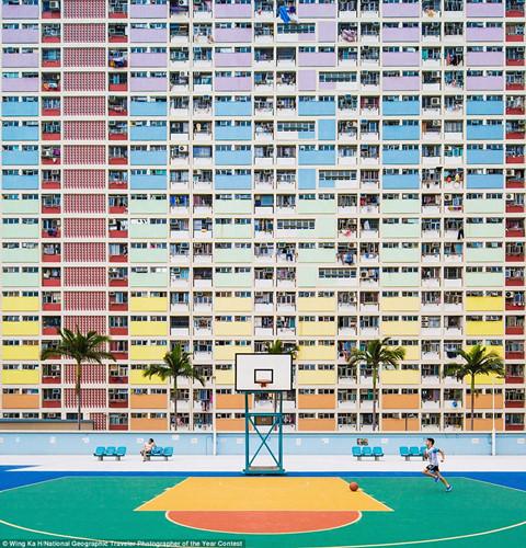 Một cậu bé chơi bóng rổ tại trường học với sân bóng tông xuyệt tông với màu sơn của tòa nhà chung cư phía sau ở Hong Kong.