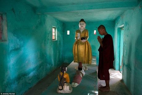 Một nhà sư đang hành lễ trong một miếu thờ ở làng Amarapura, Myanmar. Nơi đây có hàng ngàn miếu thờ như thế này.